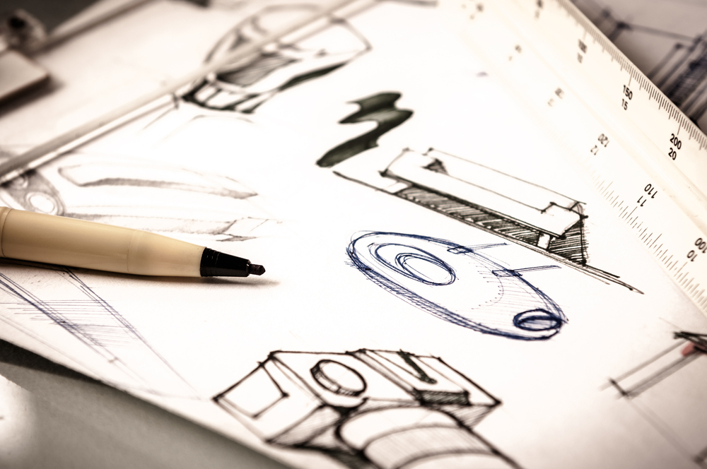 Hand drawn sketches of mechanical parts on a piece of paper.